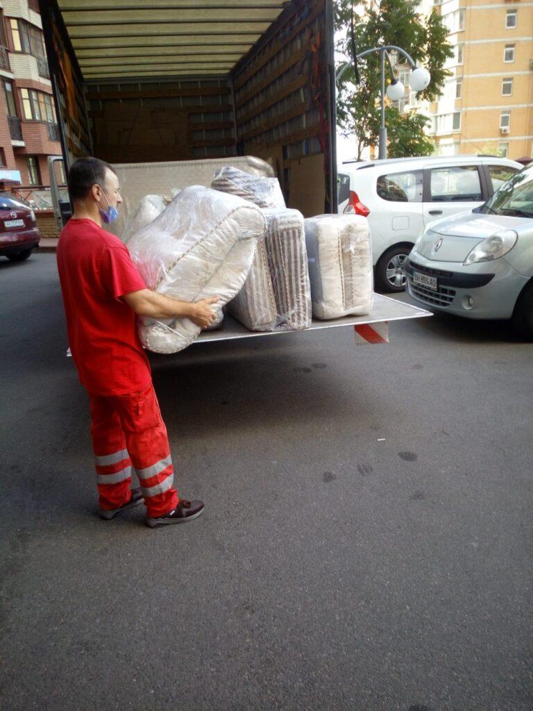 грузчик несёт мягкую мебель